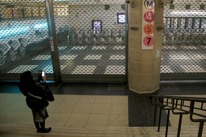 A woman pictures the closed access to the subway lines Friday, Dec.13, 2019 in Paris. French President Emmanuel Macron suggested Thursday that he was ready to make changes to his plans to overhaul the pension system as a major union warned that nationwide strikes and protests could continue unabated until Christmas. (AP Photo/Michel Euler)