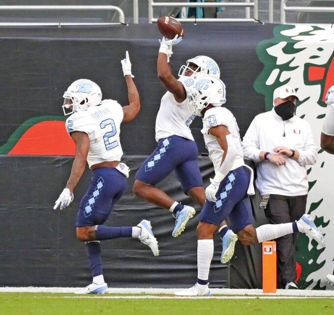 North Carolina running back Michael Carter (8) celebrates a touchdown against Miami during the first half of an during an NCAA college football game at Hard Rock Stadium In Miami Gardens, Fla, Saturday, Dec, 12, 2020. (Al Diaz/Miami Herald via AP)