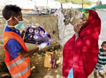 In this photo taken Wednesday, June 10, 2020, an internally-displaced Somali woman, right, is informed how to protect herself from the coronavirus, at the Weydow IDP camp in Mogadishu, Somalia. A half-year into the most momentous pandemic in decades, it's hard to imagine that anyone, anywhere hasn't heard of the coronavirus but hundreds of migrants arriving in Somalia are proving some people are still unaware of COVID-19. (Hamza Osman/International Organization for Migration (IOM) - Somalia via AP)