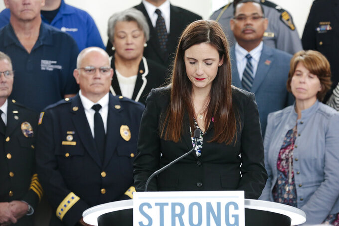 FILE- In this Oct. 7, 2019 file photo, Whitney Austin, a survivor of the September 2018 mass shooting at the Fifth Third Center in Cincinnati, becomes emotional while recounting her experience during a news conference at the Ohio Department of Public Safety in Columbus, Ohio. Although Austin has made impressive gains in her recovery from 12 close-range gunshots, progress in the former bank executive's new life's mission of combatting gun violence has been slowed by the pandemic. (Joshua A. Bickel/The Columbus Dispatch via AP)