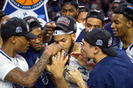 Old Dominion's B.J. Stith, center, and his teammates lean in to kiss the trophy after defeating Western Kentucky 62-56 in an NCAA college basketball game for the Conference USA men's tournament championship, Saturday, March 16, 2019, in Frisco, Texas. (AP Photo/Jeffrey McWhorter)