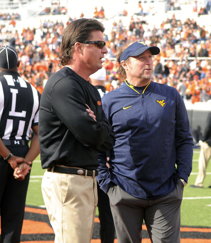 Oklahoma State head coach Mike Gundy, left, and West Virginia head coach Dana Holgorsen talk prior an NCAA college football game in Stillwater, Okla., Saturday, Nov. 17, 2018. Oklahoma State upset West Virginia 45-41. (AP Photo/Brody Schmidt)