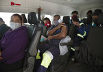 People sit in a minibus vehicle prior to be vaccinated, at the Houghton Mosque, which is being used as a drive-thru COVID-19 vaccination centre in Johannesburg Wednesday, July 28, 2021. Hitting its stride after a faltering start, South Africa's mass vaccination campaign gave jabs to 220,000 people a day last week and is accelerating toward the goal of 300,000 per day. With large deliveries of doses arriving and some vaccines being assembled here, South Africa appears on track to inoculate about 35 million of its 60 million people by the end of the year. (AP Photo/Denis Farrell)