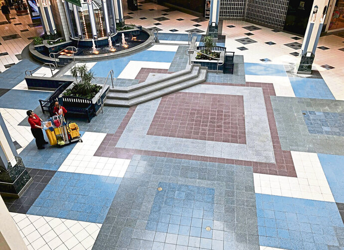 With the exception of the cleaning staff, the center court at Westmoreland Mall in Hempfield, Pa., near Pittsburgh, remains clear of large crowds on Monday, March 18, 2020, despite some businesses in the mall remaining open during the coronavirus pandemic. (Steve Adams/Pittsburgh Tribune-Review via AP)
