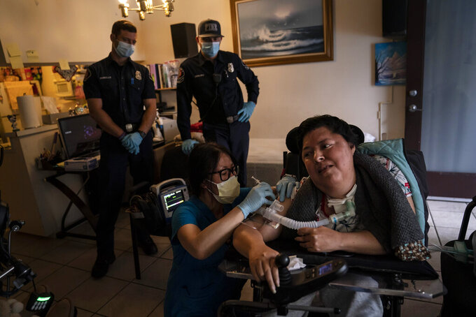 Pharmacist Stella Kim, foreground left, administers the second dose of the Pfizer COVID-19 vaccineto Socorro Franco-Martinez, who has muscular dystrophy, in her apartment as Torrance firefighters, Trevor Borello, rear left, and Alessandro Demuro watch Wednesday, May 12, 2021, in Torrance, Calif. Teamed up with the Torrance Fire Department, Torrance Memorial Medical Center started inoculating people at home in March, identifying people through a city hotline, county health department, senior centers and doctor's offices, said Mei Tsai, the pharmacist who coordinates the program. (AP Photo/Jae C. Hong)