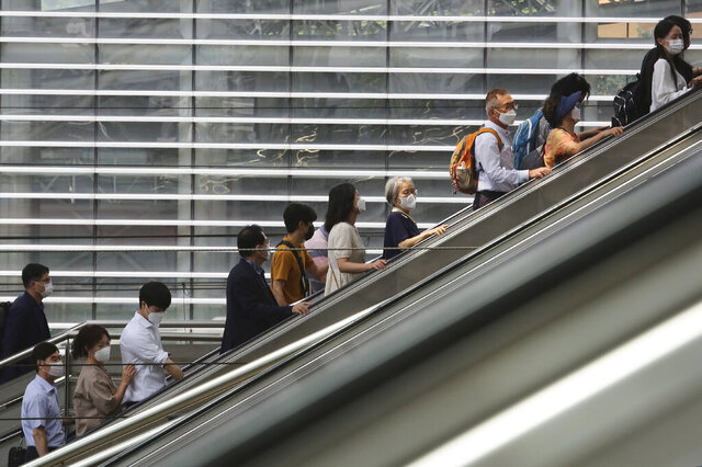 People wearing face masks to help protect against the spread of the coronavirus ride an escalator as they arrive at the Seoul Railway Station in Seoul, South Korea, Monday, Aug. 24, 2020.South Korea counted its 11th straight day of triple-digit daily jumps in coronavirus cases Monday and health officials pleaded for people to follow guidelines or risk further restrictions or strains on hospitals. (AP Photo/Ahn Young-joon)