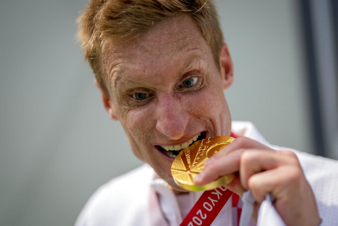Brad Snyder bites his gold medal after wining the Men's Triathlon PTV1 in the 2020 Paralympics in Tokyo, on Friday, Aug. 27, 2021. (AP Photo/Emilio Morenatti)