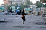 A protester does a handstand while security forces close the site of the protest during clashes in downtown Baghdad, Iraq, Thursday, Feb. 20, 2020. (AP Photo/Khalid Mohammed)