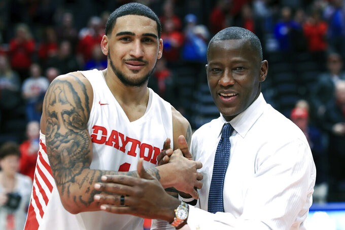 FILE - In this Feb. 22, 2020, file photo, Dayton's Obi Toppin, left, celebrates scoring his 1,000th career point with head coach Anthony Grant after an NCAA college basketball game against Duquesne, in Dayton, Ohio. Toppin and Grant have claimed top honors from The Associated Press after leading the Flyers to a No. 3 final ranking. Toppin was voted the AP men's college basketball player of the year, Tuesday, March 24, 2020. Grant is the AP coach of the year. (AP Photo/Aaron Doster, File)