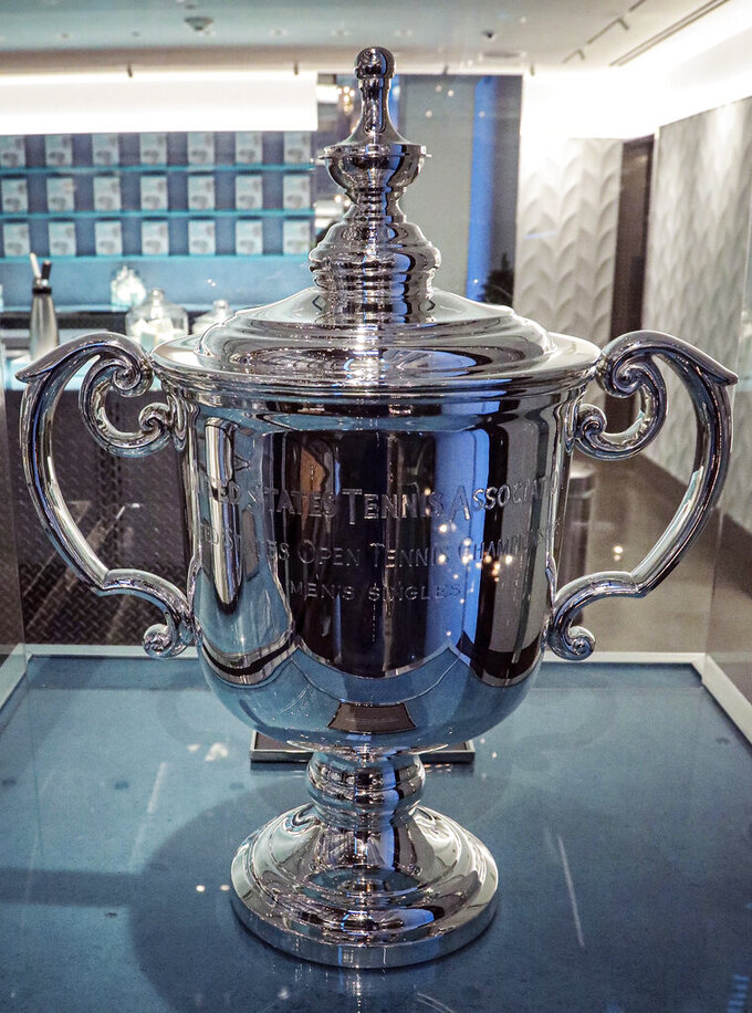 FILE - In this Dec. 6, 2019, file photo, the United States Tennis Association Men's U.S. Open Trophy, one of the world's most recognized sports trophies, is displayed at the Tiffany Men's Pop-Up store in New York. The USTA says it is overseeing a commitment of more than $50 million to help the sport deal with the effects of the coronavirus pandemic. (AP Photo/Bebeto Matthews, File)