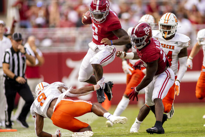 Alabama quarterback Jalen Milroe (2) leaps Mercer defensive back Michael Campbell (9) during the second half of an NCAA college football game, Saturday, Sept. 11, 2021, in Tuscaloosa, Ala. (AP Photo/Vasha Hunt)