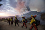 Members of firefighters crew walk in line on Sept. 5, 2020 in Yucaipa, Calif.  Firefighters trying to contain the massive wildfires in Oregon, California and Washington state are constantly on the verge of exhaustion as they try to save suburban houses, including some in their own neighborhoods.(AP Photo/Ringo H.W. Chiu)
