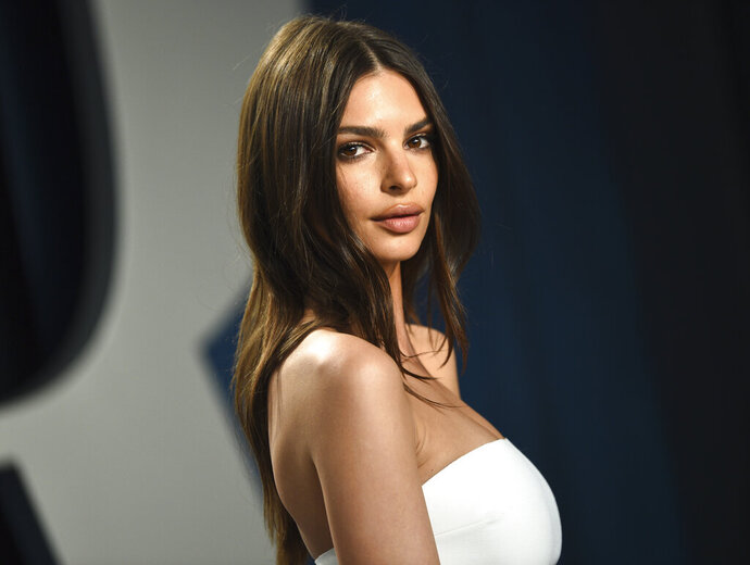"""FILE - Model Emily Ratajkowski arrives at the Vanity Fair Oscar Party in Beverly Hills, Calif., on Feb. 9, 2020. The British model and activist has a book deal. She is working on an essay collection called """"My Body."""" Metropolitan Books will publish it in 2022. (Photo by Evan Agostini/Invision/AP, File)"""