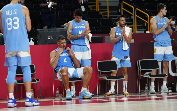 Argentina's Luis Scola (4) reacts as he receives an emotional standing ovation from his team, Australia players, and others in attendance when he was pulled from the game in the final moments of a men's basketball quarterfinal round game at the 2020 Summer Olympics, Tuesday, Aug. 3, 2021, in Saitama, Japan. (AP Photo/Eric Gay)