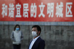 People wearing face masks to help curb the spread of the coronavirus walk by a banner which reads