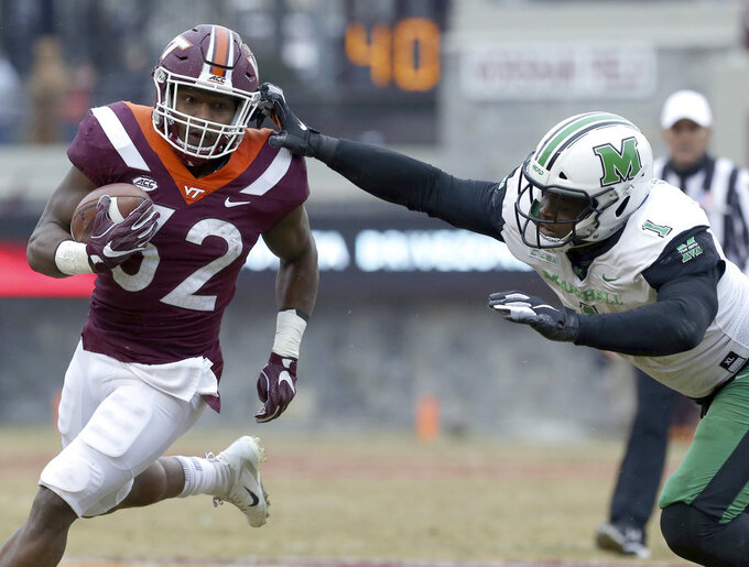 Steven Peoples (32) of Virginia Tech escapes the grasp of Ty Tyler (1) of Marshall in the second quarter of an NCAA college football game in Blacksburg Va. Saturday, Dec. 1 2018. (Matt Gentry/The Roanoke Times via AP)