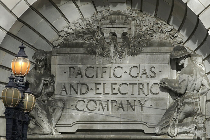 FILE - In this Oct. 10, 2019, file photo, a Pacific Gas & Electric sign is shown outside of a PG&E building in San Francisco. Pacific Gas and Electric says it has reached a $13.5 billion settlement that will resolve all major claims related to devastating wildfires blamed on its outdated equipment and negligence. The settlement, which the utility says was reached Friday, Dec. 6, 2019, still requires court approval. (AP Photo/Jeff Chiu)