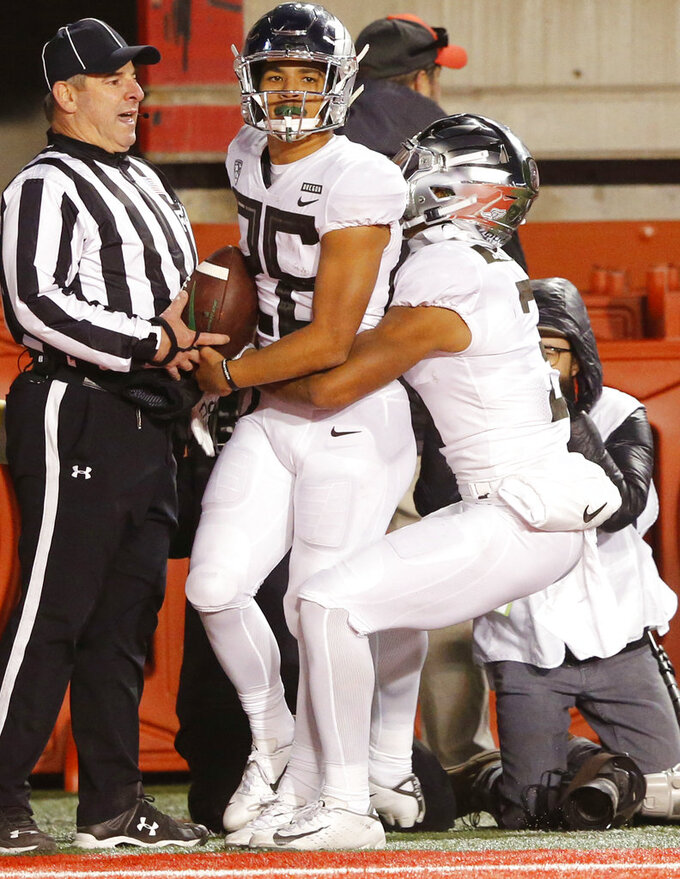 Oregon's Johnny Johnson III, right, lifts Travis Dye (26) after catching a touchdown against Utah in the second half during an NCAA college football game Saturday Nov. 10, 2018, in Salt Lake City. (AP Photo/Rick Bowmer)