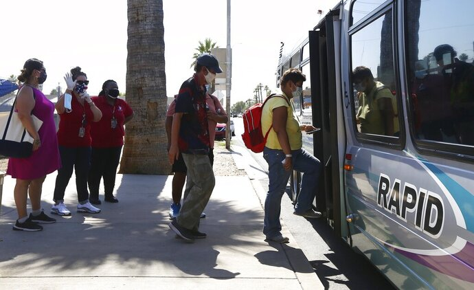 With City of Phoenix staffers helping, in red at left, patrons get on an express bus set up by the city to take people to a heat relief station inside the Phoenix Convention Center as temperatures climb to 112-degrees Friday, May 29, 2020, in Phoenix. (AP Photo/Ross D. Franklin)