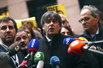 Catalonia's former regional president Carles Puigdemont, center, and former Catalan regional minister Antoni Comin, left, speak with the media as they arrive at the European Parliament in Strasbourg, eastern France, Monday, Jan. 13, 2020. Puigdemont will attend his first session as a member of the European Parliament despite facing an arrest warrant against him in Spain. (AP Photo/Francisco Seco)