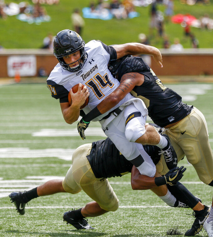 Towson quarterback Tom Flacco (14) is tackled by Wake Forest linebackers Demetrius Kemp, left, and Justin Strnad in the first half of a NCAA college football game in Winston-Salem, N.C., Saturday, Sept. 8, 2018. (AP Photo/Nell Redmond)