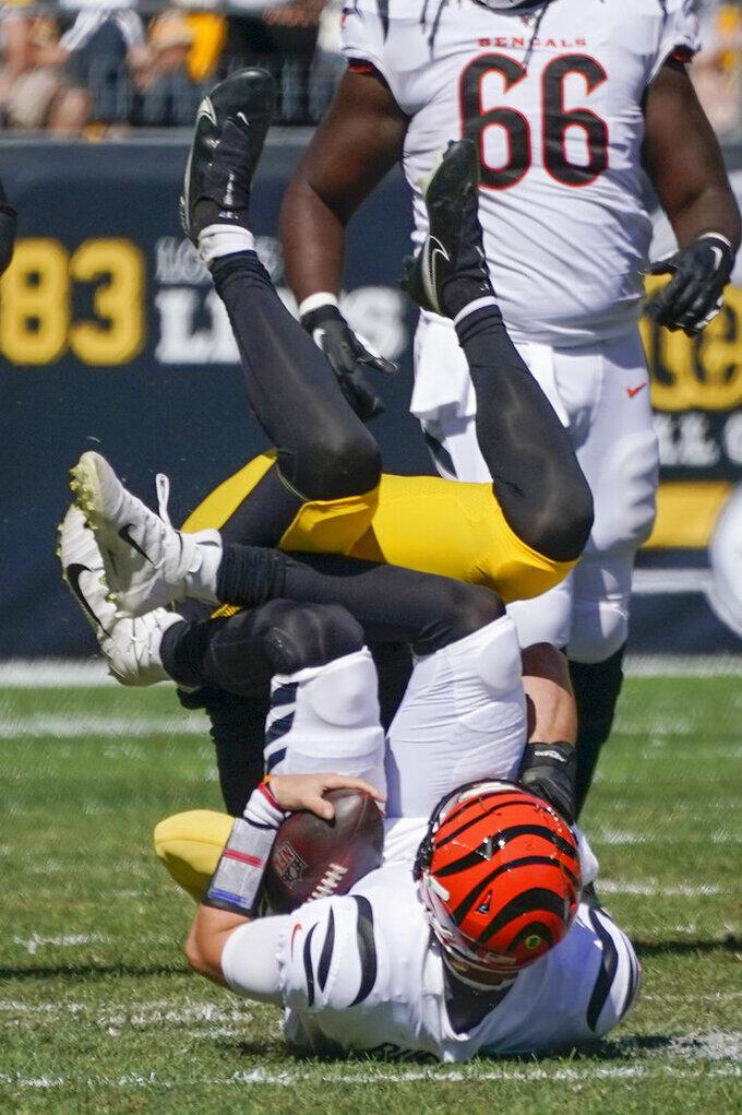 Cincinnati Bengals quarterback Joe Burrow, bottom, is tackled by Pittsburgh Steelers inside linebacker Joe Schobert after a scramble during the first half an NFL football game, Sunday, Sept. 26, 2021, in Pittsburgh. (AP Photo/Gene J. Puskar)