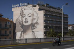 A couple on a scooter ride past a mural of Marilyn Monroe in Cannes, southern France, Tuesday, May 12, 2020. The Cannes Film Festival won't kick off as planned on Tuesday. The festival's 73rd edition has been postponed indefinitely, part of the worldwide shutdowns meant to stop the spread of the coronavirus. (AP Photo/Daniel Cole)