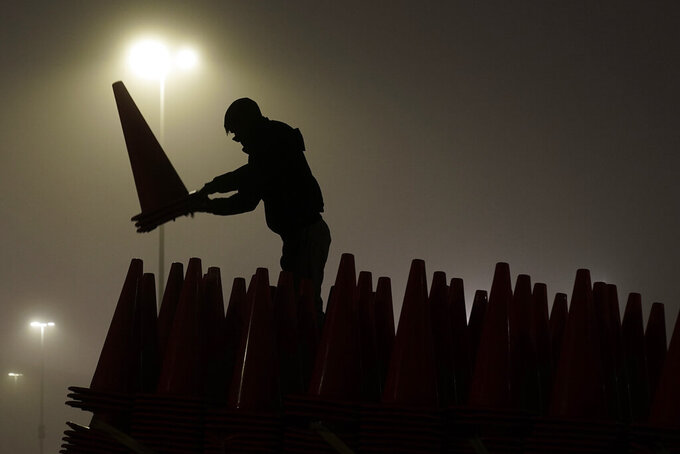 Zach Wade stacks traffic cones onto a trailer as fog envelopes a parking lot at Arrowhead Stadium after an NFL football game between the Los Angeles Chargers and the Kansas City Chiefs, Sunday, Jan. 3, 2021, in Kansas City, Mo. The cones were among 7,000 placed to block off every other parking space at the stadium in order to maintain social distancing amid the coronavirus pandemic. (AP Photo/Charlie Riedel)