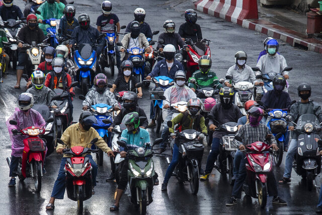 Motorcycles wearing face masks to help curb the spread of the new coronavirus wait at a stoplight in Bangkok, Thailand, Tuesday, May 26, 2020. (AP Photo/Sakchai Lalit)