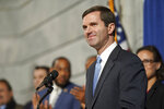 FILE- In this Dec. 12, 2019 file photo, Kentucky Gov. Andy Beshear speaks at a press conference before signing an executive order to reinstate the voting rights of over 100,000 non-violent felons who have completed their sentences, at the Capitol in Frankfort, Ky. Beshear is calling for bipartisan cooperation during a legislative session that will be dominated by work on a new two-year state budget. (AP Photo/Bryan Woolston, File)