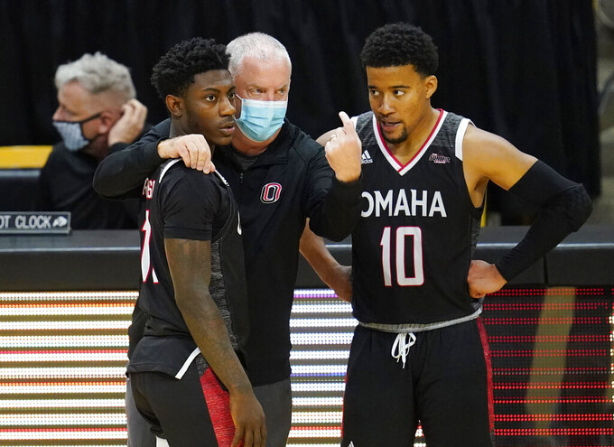Omaha head coach Derrin Hansen, center, confer with guards La'Mel Robinson, left, and Ayo Akinwole during a time out in the second half of an NCAA college basketball game against Colorado Wednesday, Dec. 16, 2020, in Boulder, Colo. Colorado won 91-49. (AP Photo/David Zalubowski)
