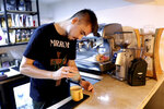 In this Monday, Oct. 7, 2019 photo, Hamed Azar, a 25-year-old Afghan refugee, makes coffee for customers at his basement Tehran coffee shop in downtown Tehran, Iran. Azar and his business partner, 21-year-old Afghan refugee Fatemeh Jafari, raised money from their parents, as well as used their own cash to open their Telma, or