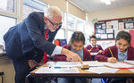 Labour leader Jeremy Corbyn talks to a student during a visit to Fulbridge Academy while on the General Election campaign trail, in Peterborough, England, Thursday, Dec. 5, 2019. Britain goes to the polls on Dec. 12. (Joe Giddens/PA via AP)