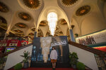 A woman poses for a souvenir photo at the lobby of the Scala theater Friday, July 3, 2020 in Bangkok, Thailand. The Scala theater has shut its doors after 51 years as a shrine for Thai movie-goers. (AP Photo/Sakchai Lalit)