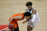 West Virginia's Miles McBride, right, tries to steal the ball from Oklahoma State's Cade Cunningham (2) during the second half of an NCAA college basketball game in the second round of the Big 12 men's tournament in Kansas City, Mo., Thursday, March 11, 2021. Oklahoma State won 72-69. (AP Photo/Charlie Riedel)