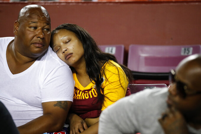 A Washington Redskins fan takes a nap on her companion's shoulder during the second half of an NFL preseason football game between the Redskins and the Cincinnati Bengals, Thursday, Aug. 15, 2019, in Landover, Md. The Bengals won 23-13. (AP Photo/Alex Brandon)
