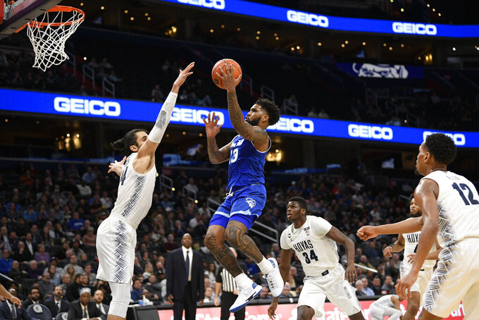 Seton Hall guard Myles Powell (13) goes to the basket against Georgetown center Omer Yurtseven, left, center Qudus Wahab (34) and guard Terrell Allen (12) during the first half of an NCAA college basketball game, Wednesday, Feb. 5, 2020, in Washington. (AP Photo/Nick Wass)