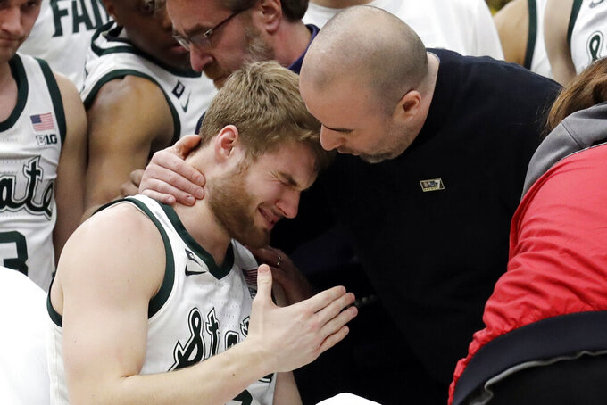 A medical personnel took talks to Michigan State's Kyle Ahrens, left, as Ahrens was the taken out of the court for injury during the first half of an NCAA college basketball championship game against Michigan in the Big Ten Conference tournament, Sunday, March 17, 2019, in Chicago. (AP Photo/Nam Y. Huh)