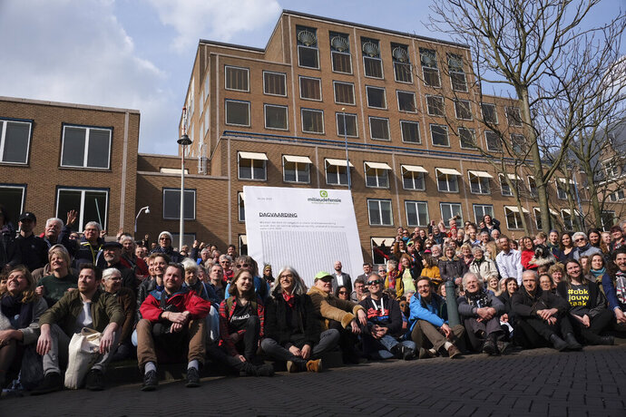 Climate activists pose outside the Shell headquarters, rear, in The Hague, Netherlands, Friday April 5, 2019, prior to deliver a court summons to Shell in a court case aimed at forcing the energy giant to do more to rein in carbon emissions. (AP Photo/Mike Corder)