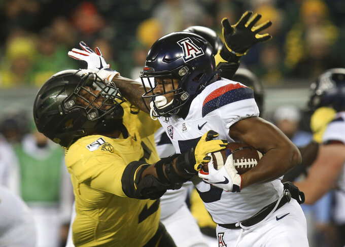 FILE - In this Nov. 16, 2019, file photo, Oregon's Kayvon Thibodeaux, left, tackles Arizona's Brian Casteel during the third quarter of an NCAA college football game, in Eugene, Ore. Thibodeaux was selected to The Associated Press All-Pac 12 Conference team, Thursday, Dec. 12, 2019. (AP Photo/Chris Pietsch, File)