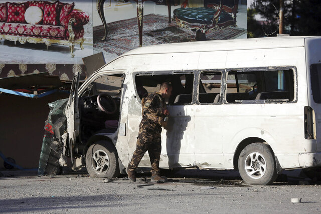 An Afghan security forces member inspects a bus carrying local TV station employees that hit a roadside bomb in Kabul, Afghanistan, Saturday, May 30, 2020. (AP Photo/Rahmat Gul)