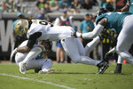 Jacksonville Jaguars quarterback Gardner Minshew, lower left, is sacked by New Orleans Saints defensive end Cameron Jordan, center, as Jaguars offensive tackle Jawaan Taylor, right, tries to slow Jordan down during the first half of an NFL football game, Sunday, Oct. 13, 2019, in Jacksonville, Fla. (AP Photo/Phelan M. Ebenhack)