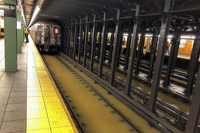 A subway train sits on flooded tracks at 66th Street, Monday, Jan. 13, 2020, in New York. A water main break flooded streets on Manhattan's Upper West Side near Lincoln Center and hampered subway service during the Monday morning rush hour. The water spread for blocks and was several inches deep in places. (AP Photo/Richard Drew)