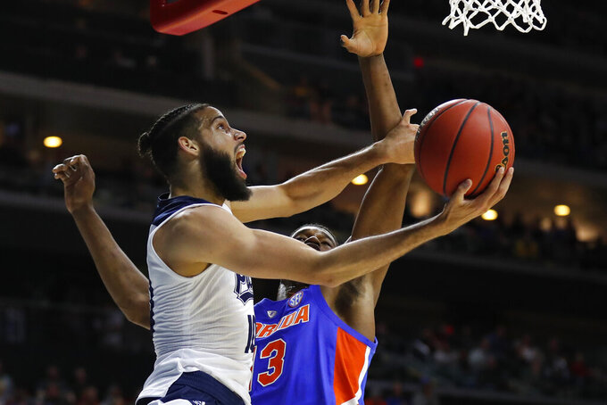 Nevada forward Caleb Martin drives to the basket past Florida center Kevarrius Hayes, rear, during a first round men's college basketball game in the NCAA Tournament, Thursday, March 21, 2019, in Des Moines, Iowa. (AP Photo/Charlie Neibergall)