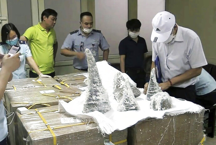 In this Thursday, July 25, 2019, photo, customs officers at Noi Bai airport discover rhino horns concealed in plaster blocks in  in Hanoi, Vietnam. Vietnam's customs authority confiscated 125 kilograms of rhino horns worth up to $4 million in an air shipment, the state-run Vietnam News reported Monday, July 29, 2019. (Nguyen Quang Hai/Vietnam News Agency via AP)