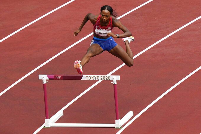Dalilah Muhammad, of United States, wins a heat in the women's 400-meter hurdles at the 2020 Summer Olympics, Saturday, July 31, 2021, in Tokyo. (AP Photo/Martin Meissner)