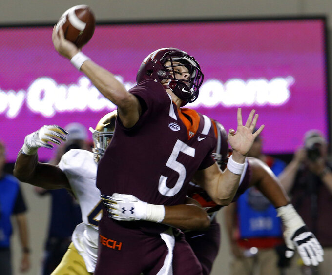 Virginia Tech quarterback Ryan Willis (5) gets off a pass as Notre Dame defensive lineman Julian Okwara, left, closes in during the first half of an NCAA college football game in Blacksburg, Va., Saturday, Oct. 6, 2018. (AP Photo/Steve Helber)