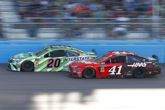 Erik Jones (20) and Daniel Suarez (41) race side-by-side during the NASCAR Cup Series auto race at ISM Raceway, Sunday, Nov. 10, 2019, in Avondale, Ariz. (AP Photo/Ralph Freso)