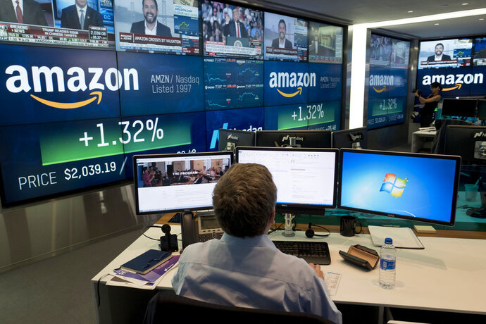 FILE- In this Sept. 4, 2018, file photo a Nasdaq employee monitors market activity in New York. Companies around the country and across industries are in the midst of reporting another quarter of gargantuan profit growth, driven by lower tax bills and a growing economy. Amazon said its net income surged more than tenfold during the summer from a year earlier, for example. (AP Photo/Mark Lennihan, File)