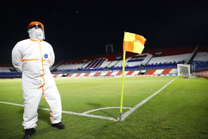 "A Conmebol worker stands guard on the pitch at the ""Defensores del Chaco"" Stadium before the start of a Copa Libertadores soccer match between Brazil's Gremio and Ecuador's Independiente del Valle, in Asuncion, Paraguay, Friday, April 9, 2021. (Natalia Aguilar/Pool via AP)"
